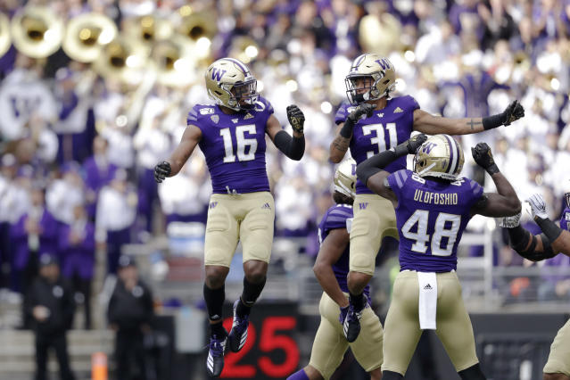 Washington's Cameron Williams (16) celebrates his interception against Southern Cal with teammate Kamren Fabiculanan (31) in the first half of an NCAA college football game Saturday, Sept. 28, 2019, in Seattle. (AP Photo/Elaine Thompson)