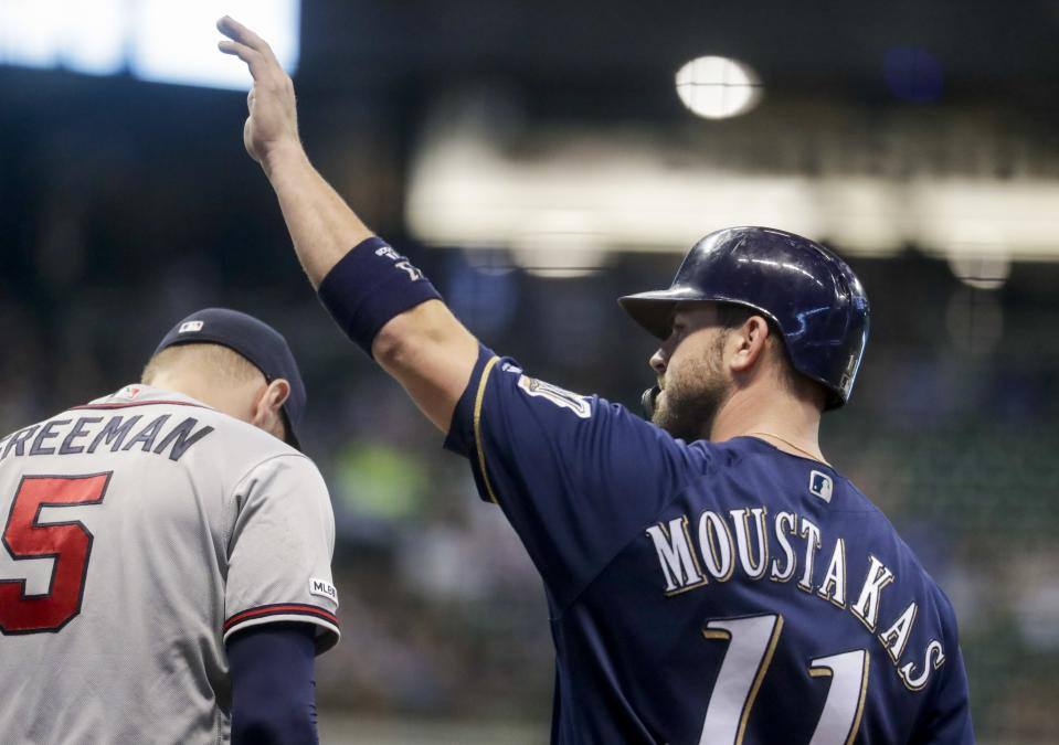 Milwaukee Brewers' Mike Moustakas waves after getting his 1,000th career hit during the seventh inning of a baseball game against the Atlanta Braves Tuesday, July 16, 2019, in Milwaukee. (AP Photo/Morry Gash)
