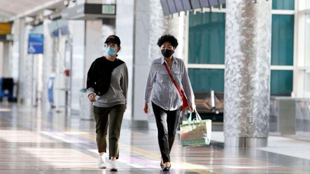 PHOTO: Two travelers wear face masks at Denver International Airport, May 3, 2020, in Denver during the coronavirus pandemic. (David Zalubowski/AP)