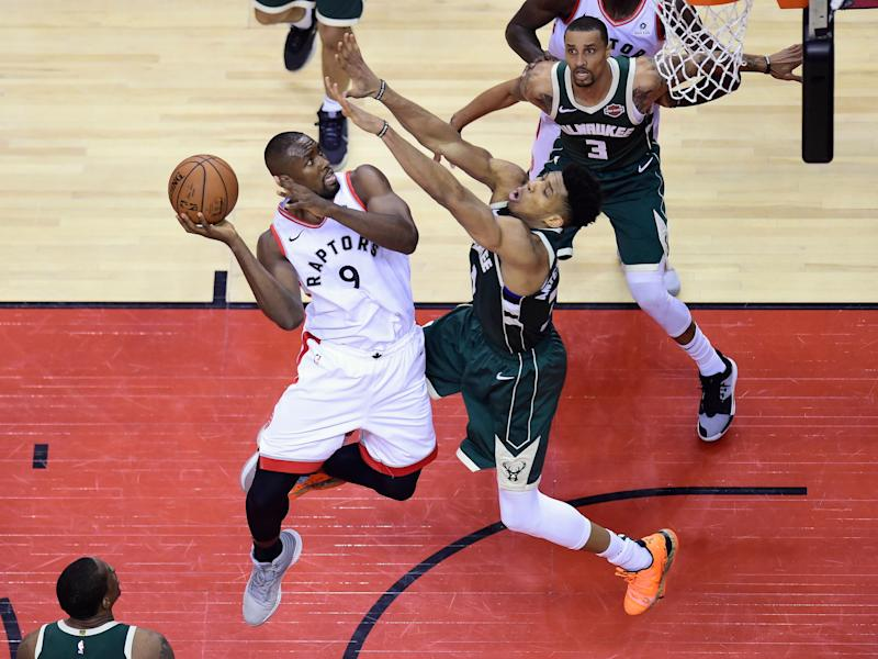 Toronto Raptors centre Serge Ibaka (9) goes the net as Milwaukee Bucks forward Giannis Antetokounmpo (34) defends during first half NBA Eastern Conference finals basketball action in Toronto on Sunday, May 19, 2019. (Frank Gunn/The Canadian Press via AP)