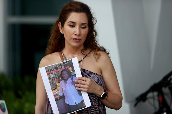 Image: Luz Marina holds a picture of her aunt, Marina Azen, who she said is missing after the partial collapse of the 12-story Champlain Towers South condo tower. (Joe Raedle / Getty Images)