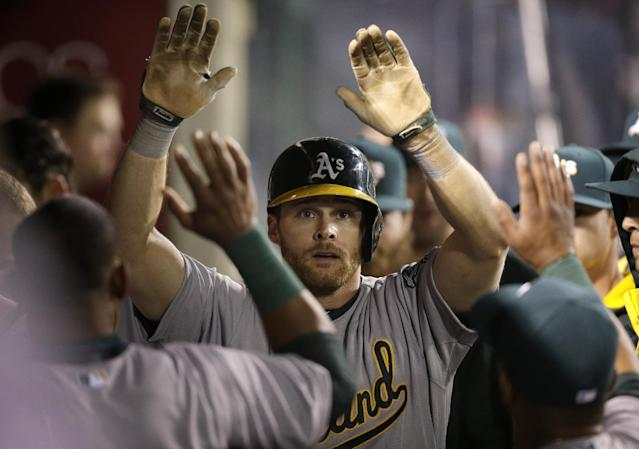 Oakland Athletics' Craig Gentry, center, is greeted by teammate after he scored on a wild pitch by Los Angeles Angels starting pitcher Garrett Richards during the seventh inning of a baseball game on Tuesday, April 15, 2014, in Anaheim, Calif. (AP Photo/Jae C. Hong)