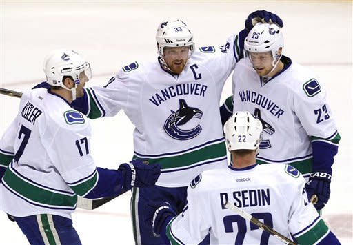 Vancouver Canucks' Alexander Edler (23), of Sweden, celebrates his goal against the Phoenix Coyotes with teammates Henrik Sedin (33), of Sweden, Ryan Kesler (17), and Daniel Sedin (22), of Sweden, during the first period in an NHL hockey game, Tuesday, Feb. 28, 2012, in Glendale, Ariz.(AP Photo/Ross D. Franklin)