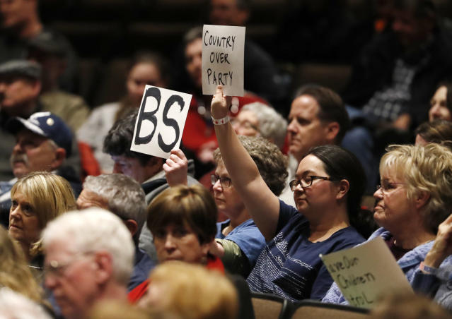 <p>Protesters hold up sign as U.S. Rep. Mike Coffman, R-Colorado, talks during a town hall meeting with constituents in a high school assembly hall Tuesday, Feb. 20, 2018, in Greenwood Village, Colo. Coffman was peppered with questions about gun control in the wake of the mass shooting at a school in south Florida last week. (Photo: David Zalubowski/AP) </p>