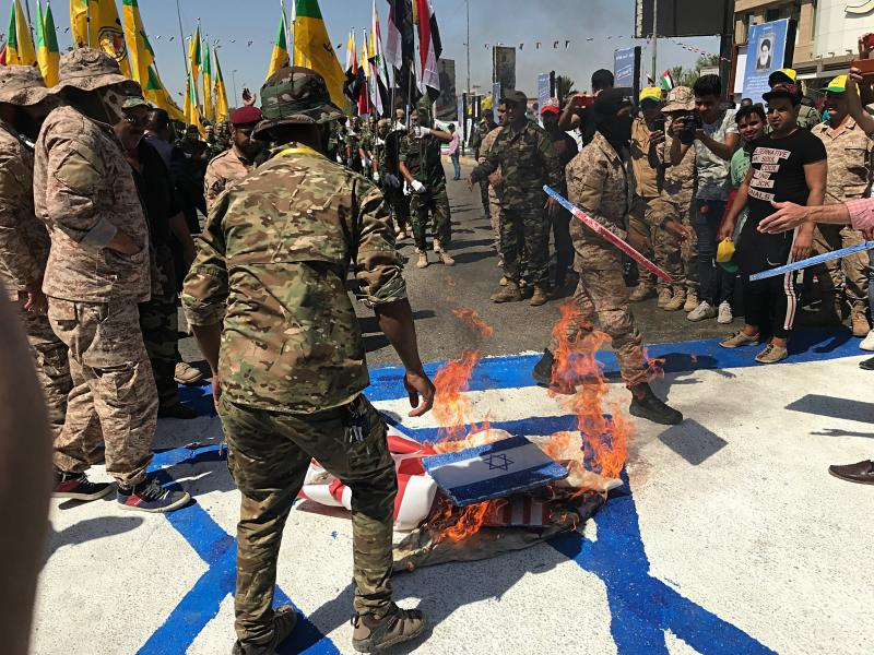 """Iraqi Popular Mobilization Forces burn representations of U.S. and Israeli flags during """"al-Quds"""" Day, Arabic for Jerusalem, in Baghdad, Iraq, Friday, May 31, 2019. Jerusalem Day began after the 1979 Islamic Revolution in Iran when the Ayatollah Khomeini declared the last Friday of the Muslim holy month of Ramadan a day to demonstrate the importance of Jerusalem to Muslims. (AP Photo/Ali Abdul Hassan)"""