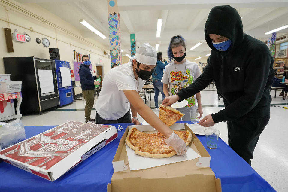 """West Brooklyn Community High School students grab slices of pizza in the cafeteria, Thursday, Oct. 29, 2020, in New York, following a current events/trivia quiz for those who showed up on a rainy day. The high school is a """"transfer school,"""" catering to a students who haven't done well elsewhere, giving them a chance to graduate and succeed. (AP Photo/Kathy Willens)"""