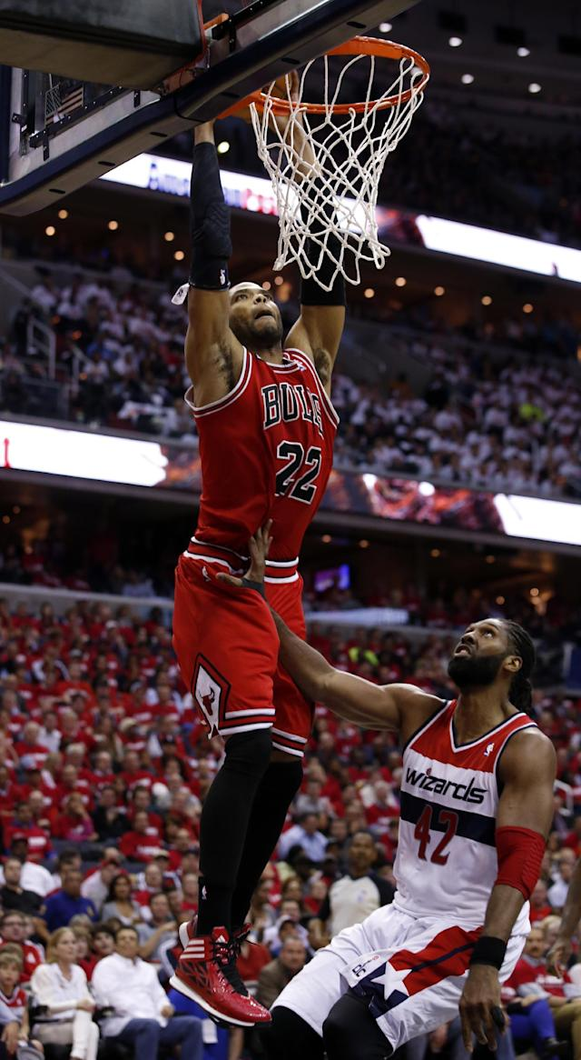 Chicago Bulls forward Taj Gibson (22) dunks in front of Washington Wizards forward Nene (42), from Brazil, in the first half of Game 3 of an opening-round NBA basketball playoff series on Friday, April 25, 2014, in Washington. (AP Photo/Alex Brandon)