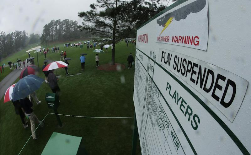 Spectators walk off the course after play was suspended because of severe weather during the first day of practice for the Masters golf tournament Monday, April 7, 2014, in Augusta, Ga. (AP Photo/Charlie Riedel)