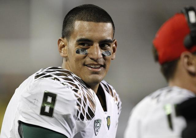 Oregon starting quarterback Marcus Mariota jokes with teammates as he watches from the sideline during the fourth quarter of Oregon's 57-16 victory over Colorado in an NCAA college football game in Boulder, Colo., on Saturday, Oct. 5, 2013. (AP Photo/David Zalubowski)