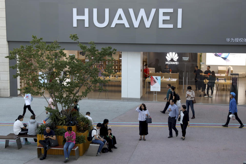 A woman gets her bearing outside a Huawei store in Beijing Monday, May 20, 2019. Google is assuring users of Huawei smartphones the American company's services still will work on them following U.S. government restrictions on doing business with the Chinese tech giant. (AP Photo/Ng Han Guan)