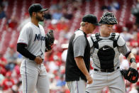 Miami Marlins starting pitcher Pablo Lopez, left, meets with pitching coach Mel Stottlemyre, center, and catcher Chad Wallach, right, after giving up a run to Cincinnati Reds' Eugenio Suarez in the fourth inning of a baseball game, Thursday, April 11, 2019, in Cincinnati. (AP Photo/John Minchillo)