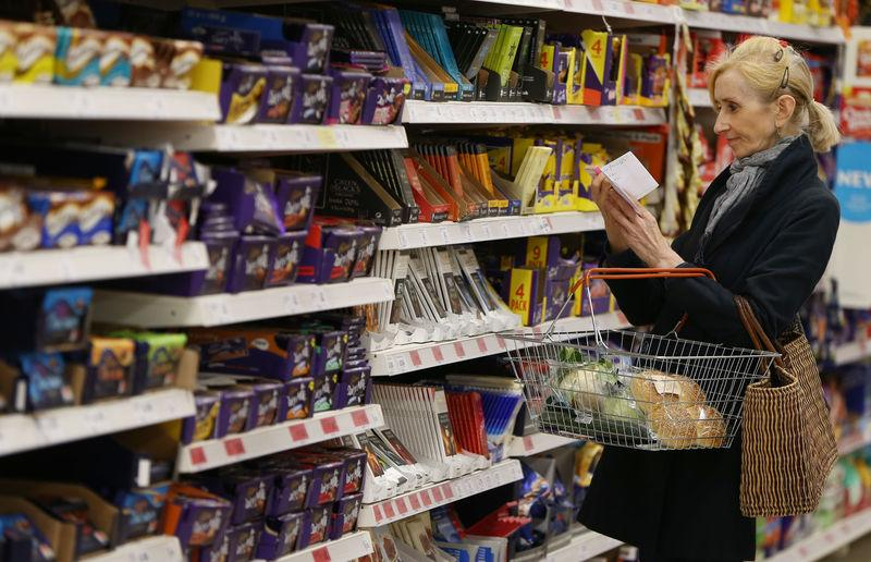 FILE PHOTO - A shopper checks her shopping list in a supermarket in London