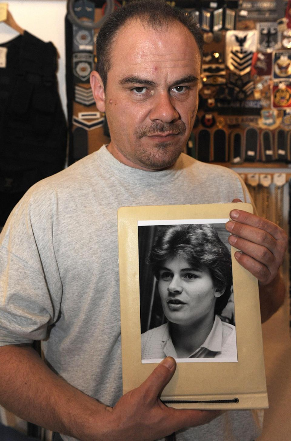 Former German shot putter Andreas Krieger, who competed as a woman (Heidi Krieger) on the East German athletics team, poses with a picture of himself in 1987 during an interview in Magdeburg, September 22, 2009 (AFP Photo/John Macdougall)