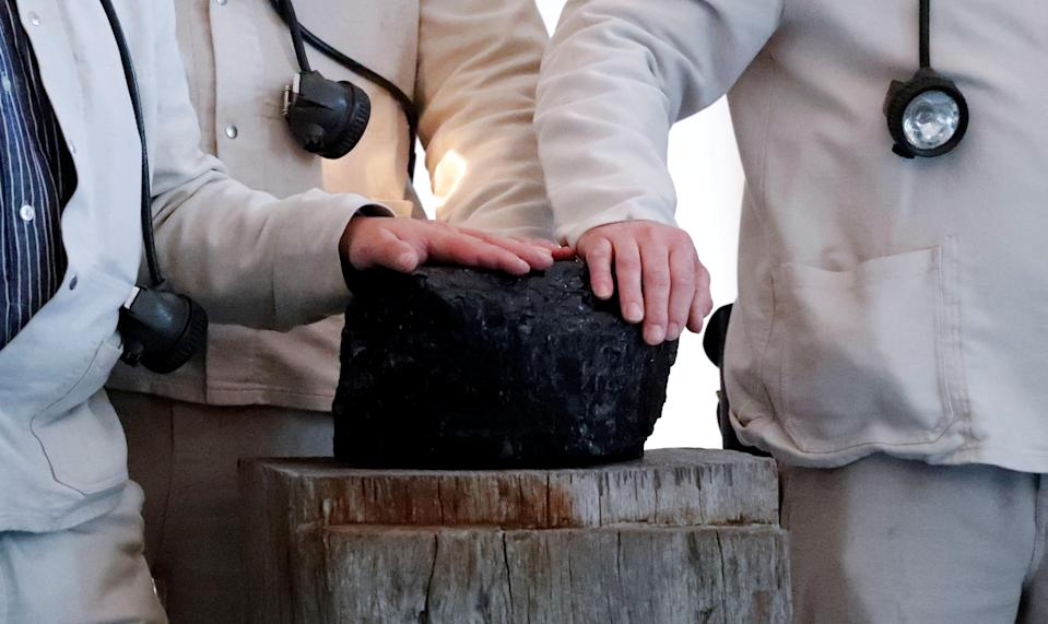 FILE PHOTO: Miners touch the symbolic last piece of stone coal harvested in a German mine to mark the end of coal mining in Germany after it was handed over to German President Frank-Walter Steinmeier at Bellevue palace in Berlin