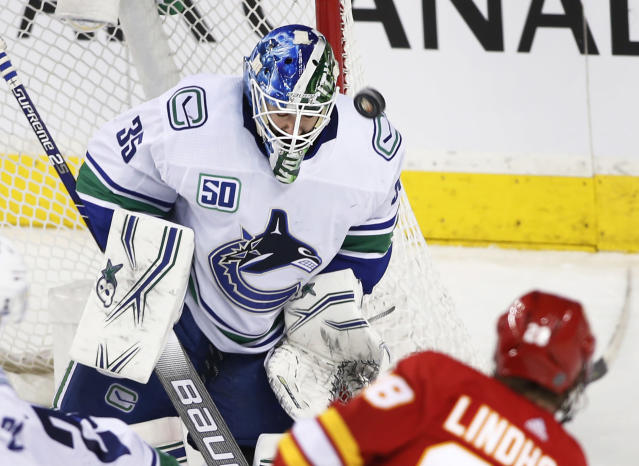 Vancouver Canucks goalie Thatcher Demko makes a save against Calgary Flames Elias Lindholm, from Sweden, during the second period of an NHL hockey game in Calgary, Alberta, Sunday, Dec. 29, 2019. (Larry MacDougal/The Canadian Press via AP)