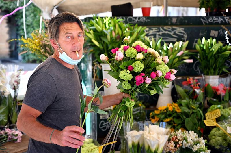 A flower seller poses on May 5, 2020 in central Rome, during the country's lockdown aimed at curbing the spread of the COVID-19 infection, caused by the novel coronavirus. (Photo by Alberto PIZZOLI / AFP) (Photo by ALBERTO PIZZOLI/AFP via Getty Images)