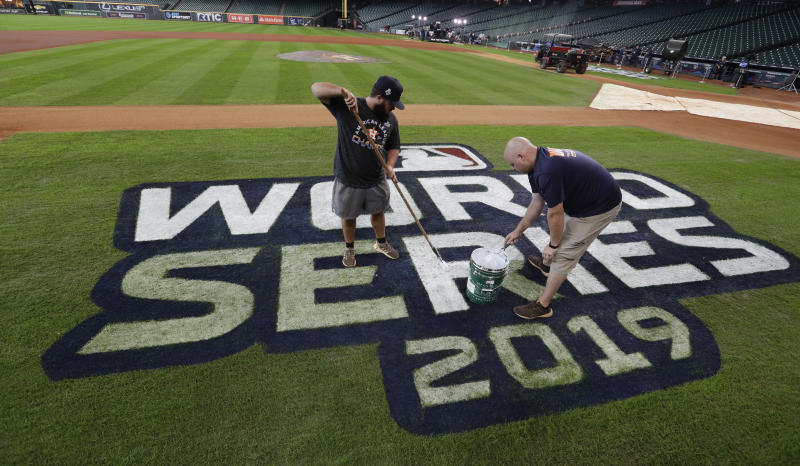 Houston Astros grounds crew members Jake Cooley, left, and Trey Feltch repaint the World Series logo for the baseball World Series at Minute Maid Park, Monday, Oct. 28, 2019. The Astros will play the Washington Nationals in Game 6 on Tuesday. (AP Photo/Eric Gay)