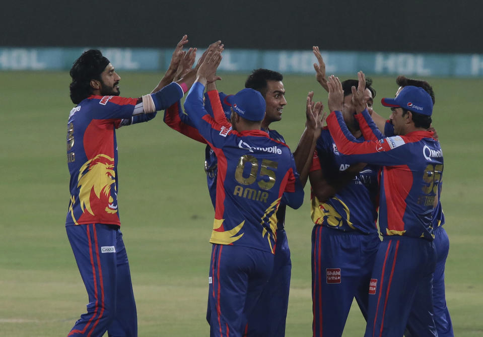 Karachi Kings pacer Umaid Asif, left, celebrates with teammates after taking the wicket of Qalandars batsman Tamim Iqbal during the final of Pakistan Super League T20 cricket match at National Stadium in Karachi, Pakistan, Tuesday, Nov. 17, 2020. (AP Photo/Fareed Khan)