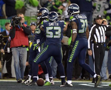 Jan 19, 2014; Seattle, WA, USA; Seattle Seahawks outside linebacker Malcolm Smith (53) celebrates with cornerback Richard Sherman (25) and strong safety Kam Chancellor (31) after intercepting a pass in the end zone in the fourth quater of the 2013 NFC Championship football game against the San Francisco 49ers at CenturyLink Field. Kirby Lee-USA TODAY Sports