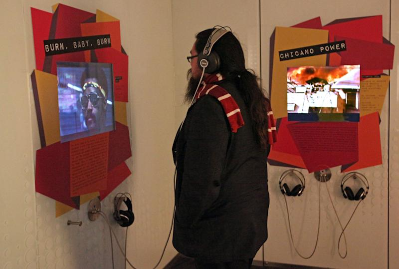 "This March 26, 2012 photo shows a visitor listening to music and spoken word recordings at an interactive exhibit about the 1965 Watts Riots at ""Trouble In Paradise: Music and Los Angeles, 1945-1975,"" at the Grammy Museum in downtown Los Angeles. The museum website says the exhibit focuses on the ""tensions between alluring myths of Southern California paradise and the realities of social struggle that characterized the years following WWII."" (AP Photo/Reed Saxon)"