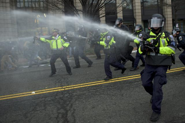 Police dispense pepper spray after a limousine was set on fire during the protests. (Mark Makela/Getty Images)