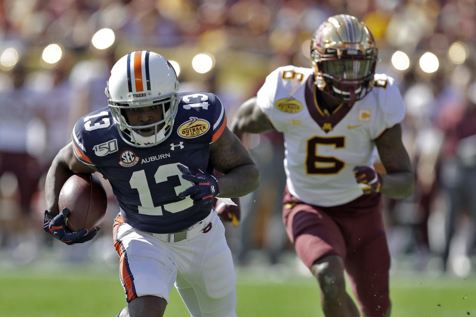 Auburn defensive back Javaris Davis (13) runs with the football after intercepting a pass intended for Minnesota wide receiver Tyler Johnson (6) during the first half of the Outback Bowl NCAA college football game Wednesday, Jan. 1, 2020, in Tampa, Fla. (AP Photo/Chris O'Meara)