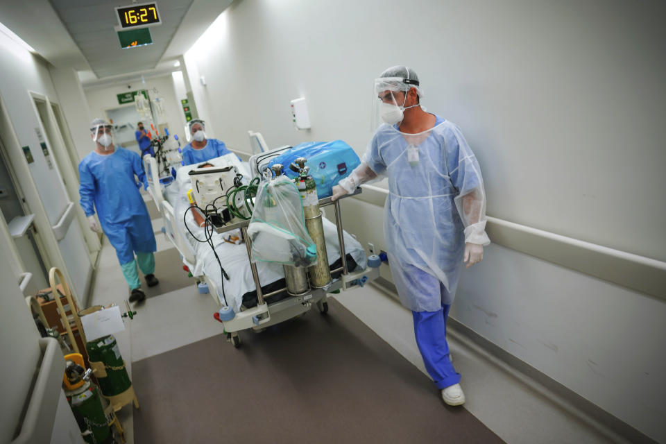 Healthcare workers transport a COVID-19 patient in an intensive care unit at the Hospital das Clinicas in Porto Alegre, Brazil, Friday, March 19, 2021. (AP Photo/Jefferson Bernardes)