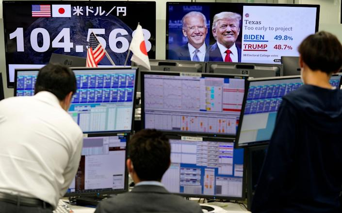 Currency traders in Tokyo were glued to their TVs this morning - EPA