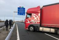 Migrants face off with a trucker on the A16 highway near Calais