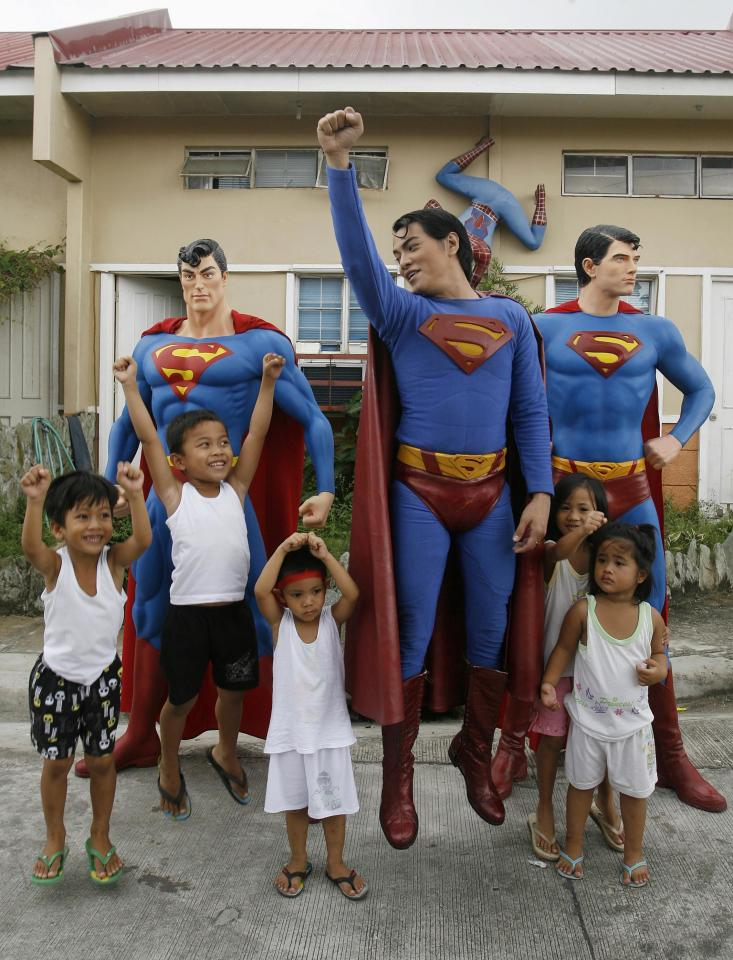 "Herbert Chavez poses with his life-sized Superman staues with children outside his house in Calamba Laguna, south of Manila October 12, 2011. In his idolization of the superhero, Chavez, a self-professed ""pageant trainer"" who owns two costume stores, has undergone a series of cosmetic surgeries for his nose, cheeks, lips and chin down to his thighs and even his skin color to look more like the ""Man of Steel"". The final result bears little resemblance to his old self. REUTERS/Cheryl Ravelo (PHILIPPINES - Tags: SOCIETY)"