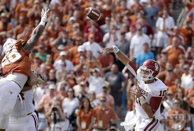 Oklahoma quarterback Blake Bell (10) passes against a leaping Texas defensive end Cedric Reed (88) during the first half of an NCAA college football game at the Cotton Bowl Saturday, Oct. 12, 2013, in Dallas. (AP Photo/Brandon Wade)