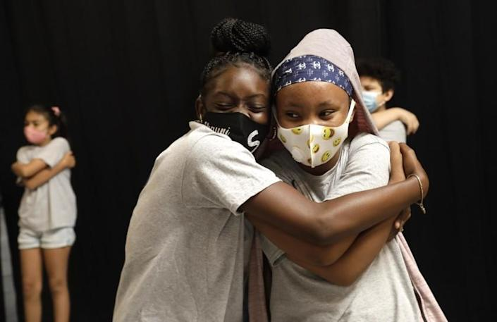 SOUTH LOS ANGELES, CA - JULY 15, 2021 - - Shauni Edmund, 13, left, and Ty'lir Langston, 11, hug during a mindfulness exercise before learning practical skills in technology at a tech summer camp at SoLA Impact's new Tech and Entrepreneurship CenterThe Beehive in South Los Angeles on July 15, 2021. Children learn animation, digital storytelling, video game design, Photoshop, coding and website design at the tech summer camp. The tech summer camp has been held over the last month, impacting about 100 local youth. Mayor Eric Garcetti visited The Beehive with other dignitaries and philanthropists. The event aims to highlight the practical ways that private, public and institutional capital can positively impact minority communities in South and East Los Angeles. (Genaro Molina / Los Angeles Times)