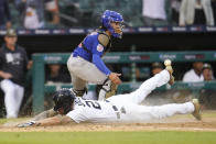 Detroit Tigers' JaCoby Jones slides safely into home plate to score on a Harold Castro single as Chicago Cubs catcher Tony Wolters (11) waits for the throw in the 10th inning of a baseball game in Detroit, Saturday, May 15, 2021. Detroit won 9-8. (AP Photo/Paul Sancya)