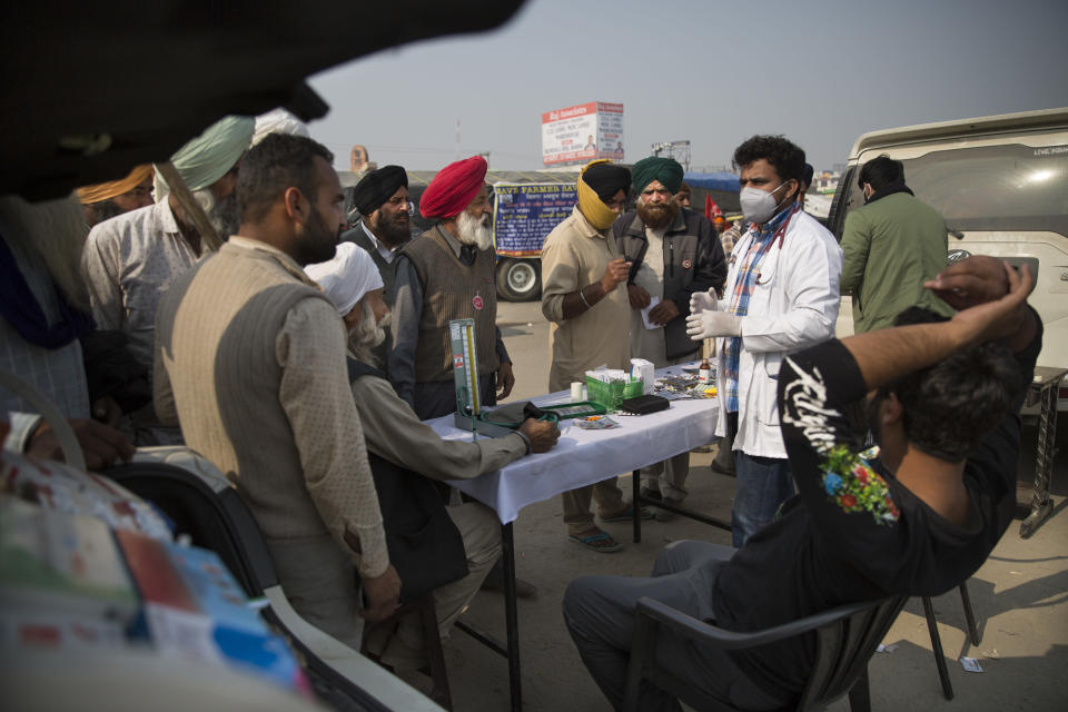 "Farmers crowd a doctor who has volunteered his services during a protest against new farming laws they say will result in exploitation by corporations, eventually rendering them landless, at the Delhi-Haryana state border, India, Tuesday, Dec. 1, 2020. The busy, nonstop, arterial highways that connect most northern Indian towns to this city of 29 million people, now beat to the rhythm of never-heard-before cries of ""Inquilab Zindabad"" (""Long live the revolution""). Tens and thousands of farmers, with colorful distinctive turbans and long, flowing beards, have descended upon its borders where they commandeer wide swathes of roads. (AP Photo/Altaf Qadri)"