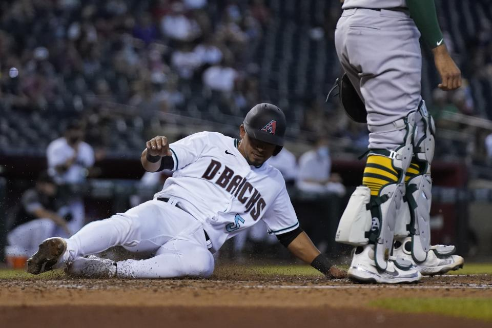 Arizona Diamondbacks' Eduardo Escobar scores a run against the Oakland Athletics during the third inning of a baseball game Tuesday, April 13, 2021, in Phoenix. (AP Photo/Ross D. Franklin)