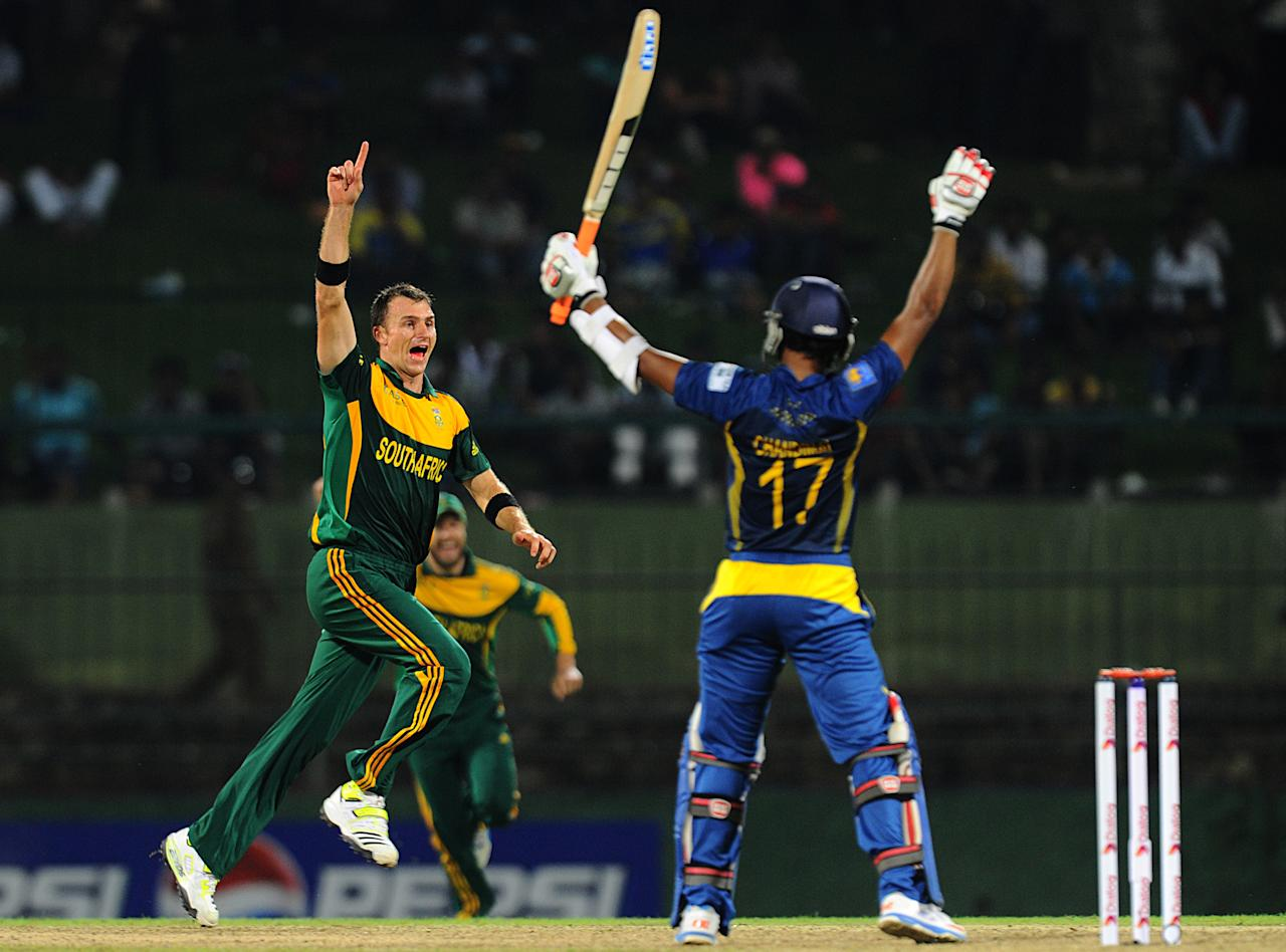 South African cricketer Ryan McLaren (L) celebrates with his teammates after he dismissed Sri Lankan batsman  Dinesh Chandimal (R) during the third One Day International (ODI) cricket match between Sri Lanka and South Africa at the Pallekele International Cricket Stadium in Pallekele on July 26, 2013. AFP PHOTO/ Ishara S.KODIKARA        (Photo credit should read Ishara S.KODIKARA/AFP/Getty Images)