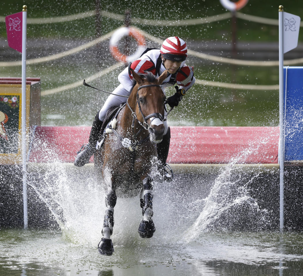 Takayuki Yumira of Japan rides Latina as he competes in the equestrian eventing cross country phase at Greenwich Park, at the 2012 Summer Olympics, Monday, July 30, 2012, in London. (AP Photo/Markus Schreiber)