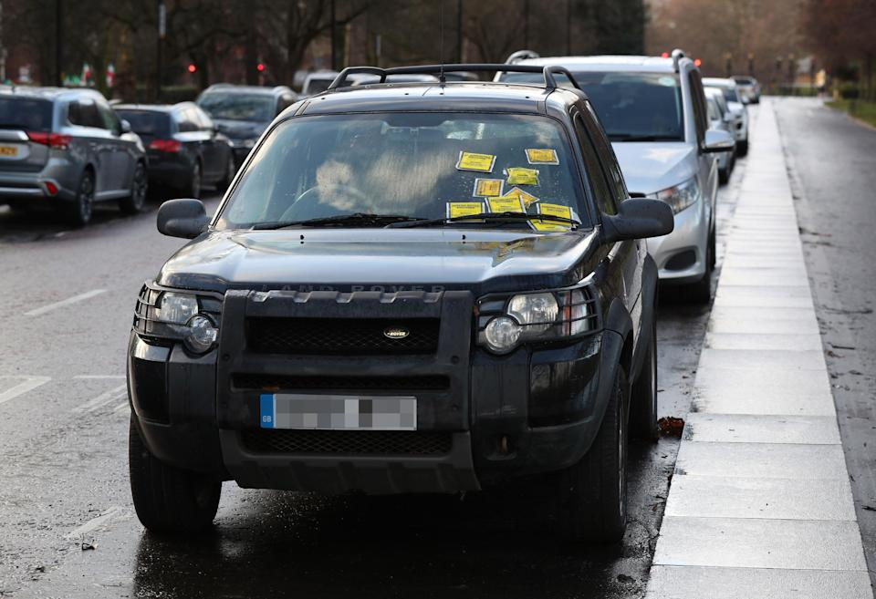 Parking Notice fixed penalties are attached to the windscreen of a Land Rover Freelander on South Carriage Drive in Hyde Park, London