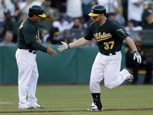 Oakland Athletics' Brandon Moss, right, is congratulated by third base coach Mike Gallego after hitting a two run home run off New York Yankees' Phil Hughes in the second inning of a baseball game on Wednesday, June 12, 2013, in Oakland, Calif. (AP Photo/Ben Margot)