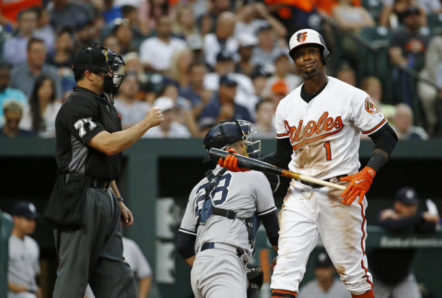 Baltimore Orioles' Tim Beckham, right, walks off the field past umpire Jim Reynolds and New York Yankees catcher Austin Romine after striking out swinging during the third inning of a baseball game Wednesday, July 11, 2018, in Baltimore. (AP Photo/Patrick Semansky)