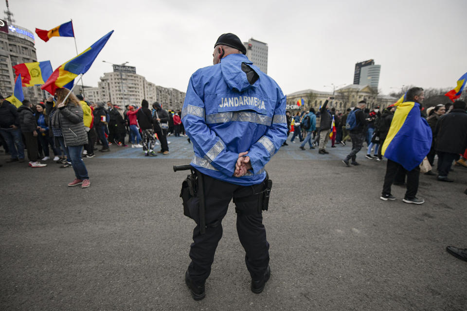 A riot policeman stands as people arrive outside the government headquarters during a protest against the COVID-19 pandemic restrictions in Bucharest, Romania, Saturday, April 3, 2021. Anti-restriction protesters have taken to the streets in several Romanian cities against new pandemic measures that came into force a day earlier amid rising COVID-19 infections. More than a thousand people gathered in the capital of Bucharest. (AP Photo/Andreea Alexandru)