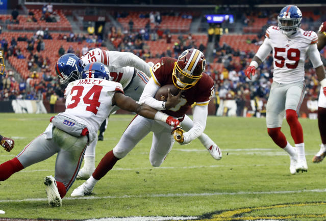 Washington Redskins quarterback Josh Johnson (8) scores a touchdown past New York Giants defensive back Grant Haley (34) during the second half of an NFL football game Sunday, Dec. 9, 2018, in Landover, Md. (AP Photo/Patrick Semansky)