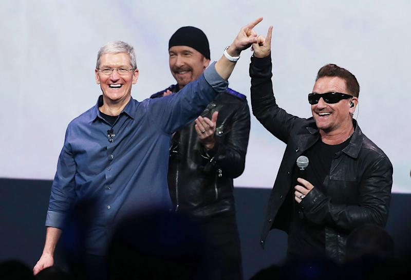 Apple CEO Tim Cook (L) greets the crowd with U2 singer Bono (R) during an Apple special event at the Flint Center for the Performing Arts on September 9, 2014 in Cupertino, California