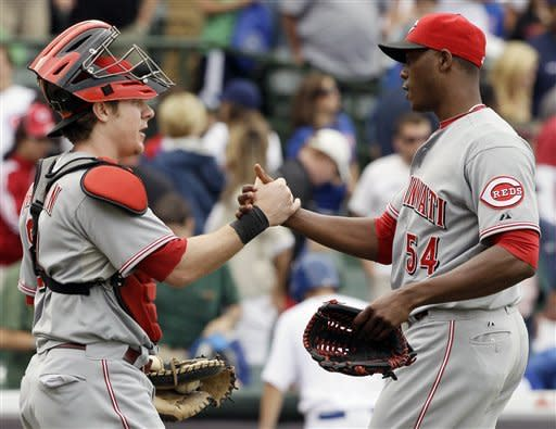 Cincinnati Reds closer Aroldis Chapman, right, celebrates with catcher Ryan Hanigan after they defeated the Chicago Cubs 10-8 in a baseball game in Chicago, Friday, Aug. 10, 2012. (AP Photo/Nam Y. Huh)
