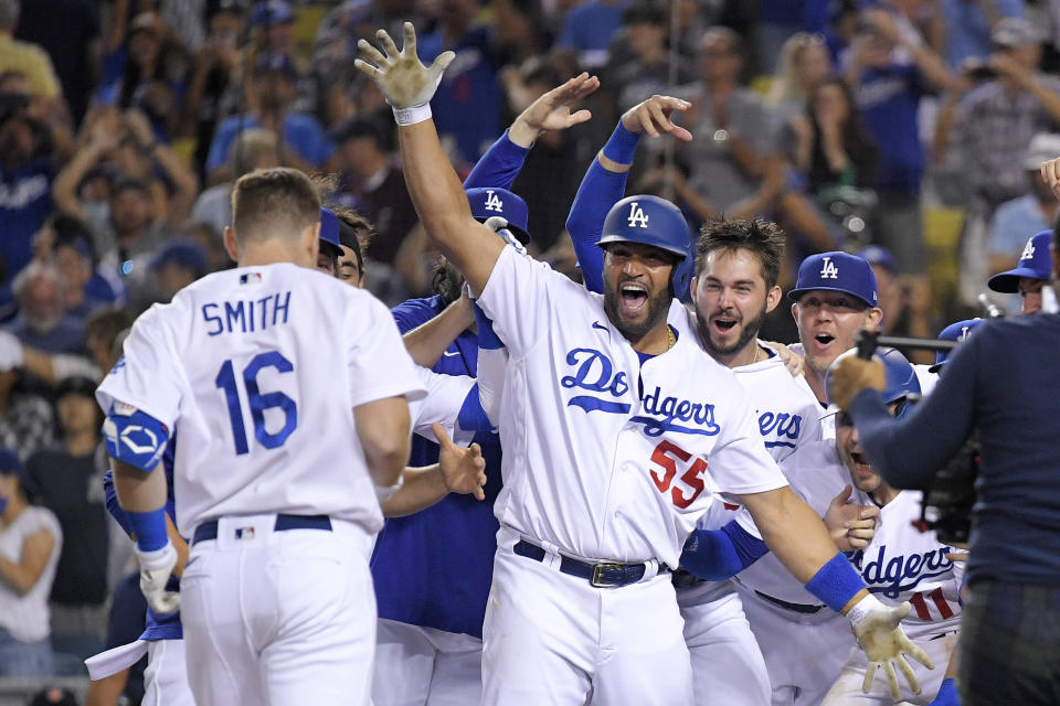 Members of the Los Angeles Dodgers celebrate as Will Smith, left, score after hitting a three-run walk off home run during the ninth inning of a baseball game against the San Francisco Giants Tuesday, July 20, 2021, in Los Angeles. (AP Photo/Mark J. Terrill)