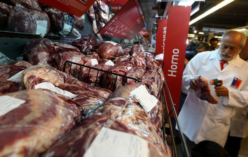 A member of the Public Health Surveillance Agency measures the temperature where the products are exposed at a supermarket after the Chilean government suspended all meat and poultry imports from Brazil, in Santiago,