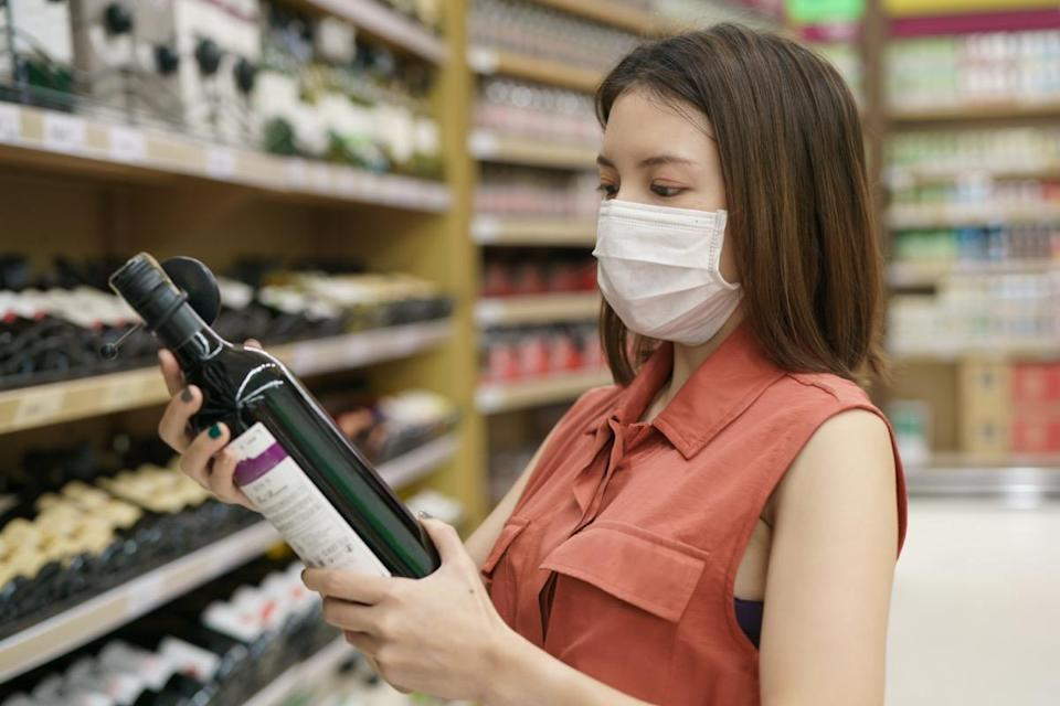 Woman in medical protective mask panic buying wine