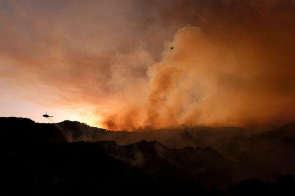 PHOTO: A helicopter drops water as smoke rises from a brush fire in the Pacific Palisades area of Los Angeles, May 15, 2021.  (Ringo H.w. Chiu/AP)