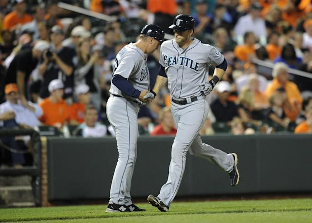 Seattle Mariners' Michael Saunders, right, is greeted by third base coach Daren Brown, left, as he rounds the bases after a three-run home run against the Baltimore Orioles during the fifth inning of a baseball game, Saturday, Aug. 3, 2013, in Baltimore. (AP Photo/Nick Wass)