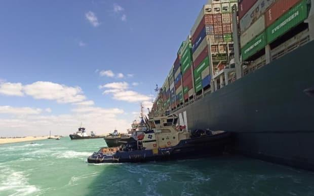 A Robert Allan designed tugboat owned by Danish company Svitzer pushes the MV Ever Given in the Suez Canal.